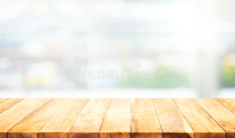Wood table top on blur white glass wall background. Form office building. For montage product display and design key visual layout stock photo