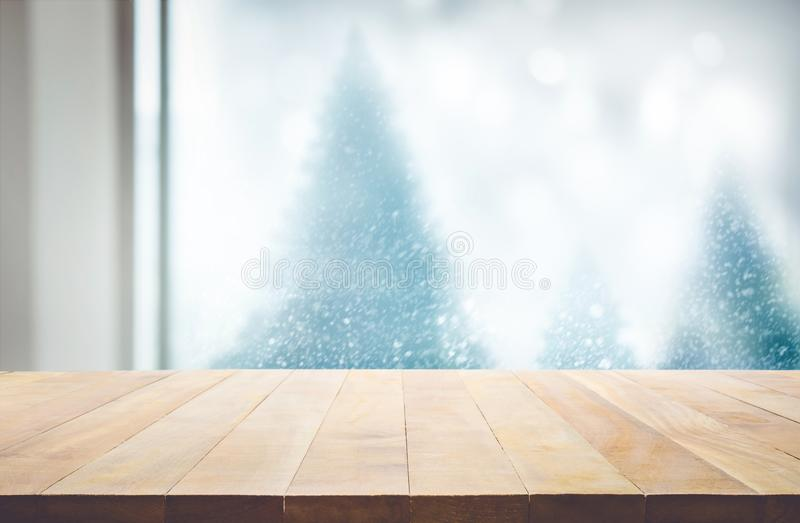 Wood table top on blur window view with pine tree in snow fall o. F morning winter season.For christmas day background and new year concepts royalty free stock photos