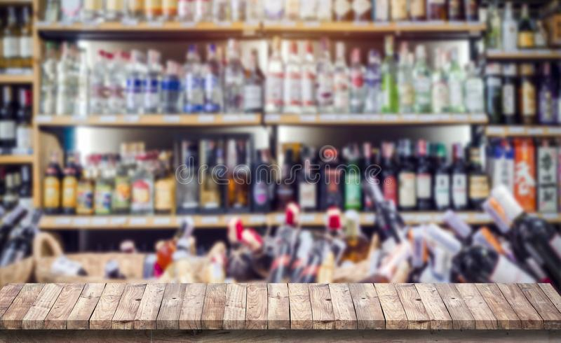 Wood table top with blur of wine bottle on shelf in supermarket. Background for product display stock images