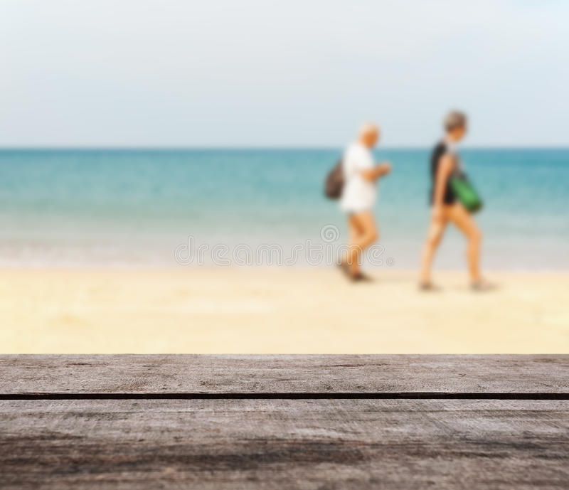 Wood table top on blurred blue sea and white sand beach royalty free stock images