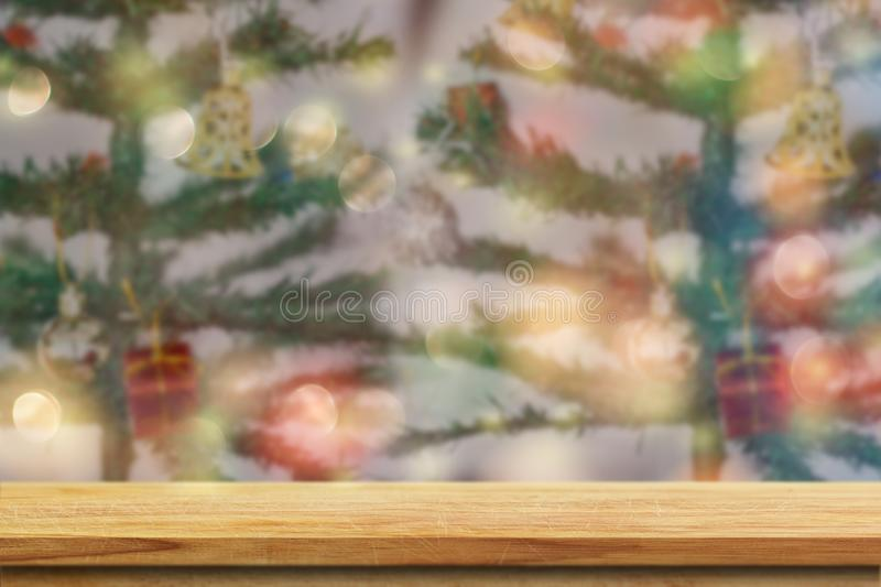 Wood table top on blurred colorful Christmas tree. And bokeh background, for display or montage products stock image