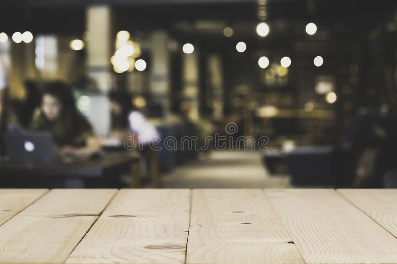 Wood Table top Counter with blurred of coffee shop. Wood Table top Counter with blurred of coffee shop or modern library . Abstract, freelancer working on royalty free stock photo