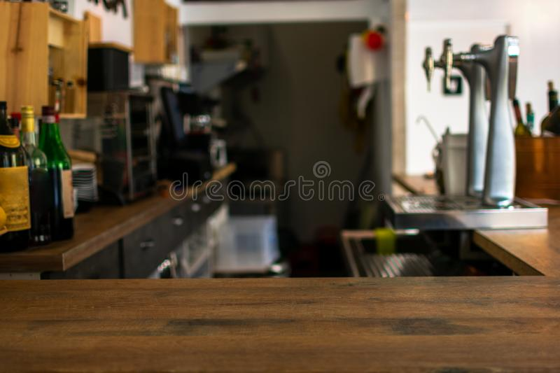 Wood table top counter with defocused background of restaurant, bar or cafeteria royalty free stock image