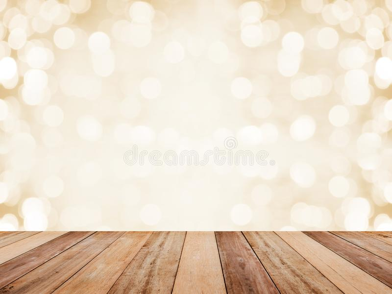 Wood table top over abstract golden background with white bokeh for Christmas and new year holidays. Montage style to display the. Product stock photography