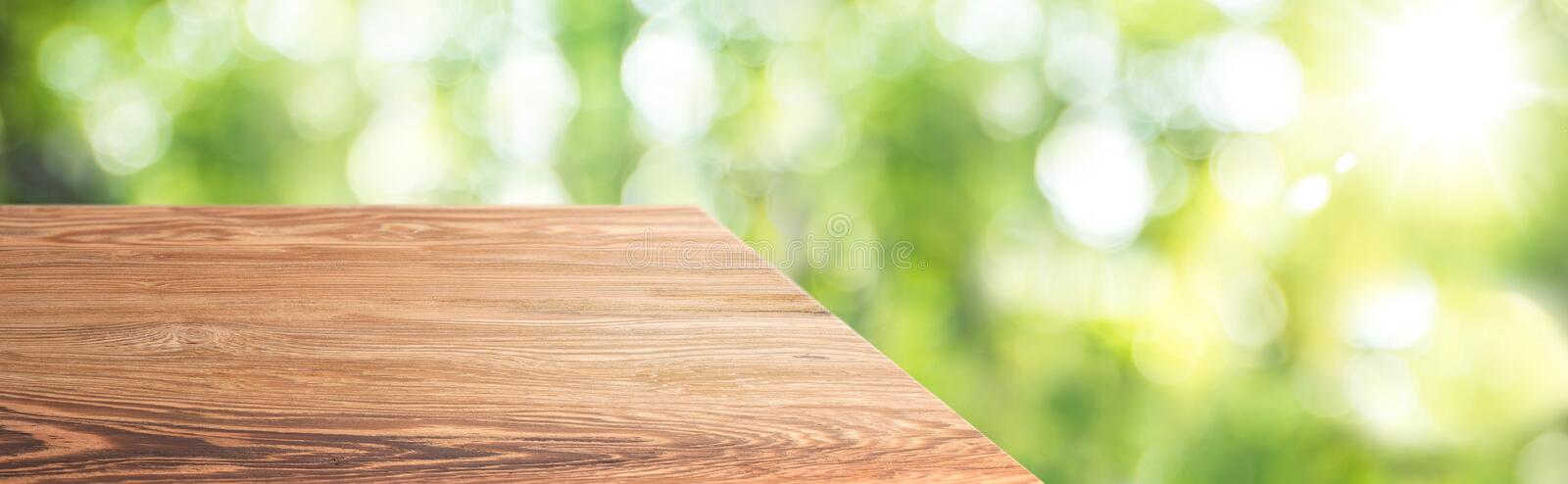 Wood table top product display background with blur nature garden.left perspective wooden kitchen counter with green leaf and stock photo