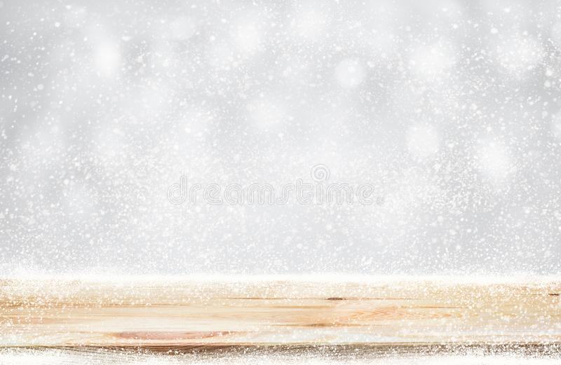 Wood table top with snowfall of winter season background.christmas royalty free stock photo