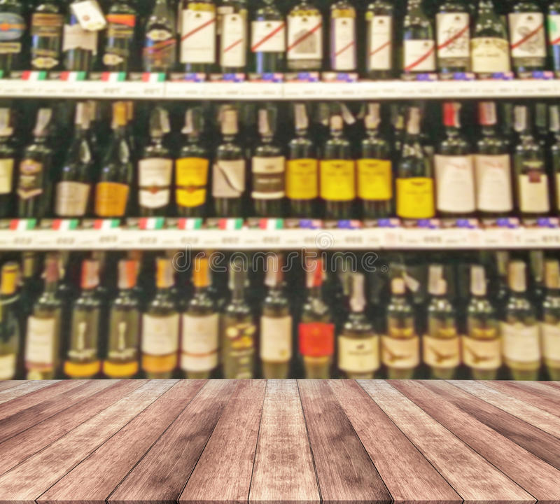 Wood table and wine Liquor bottle on shelf. Blurred background royalty free stock photography