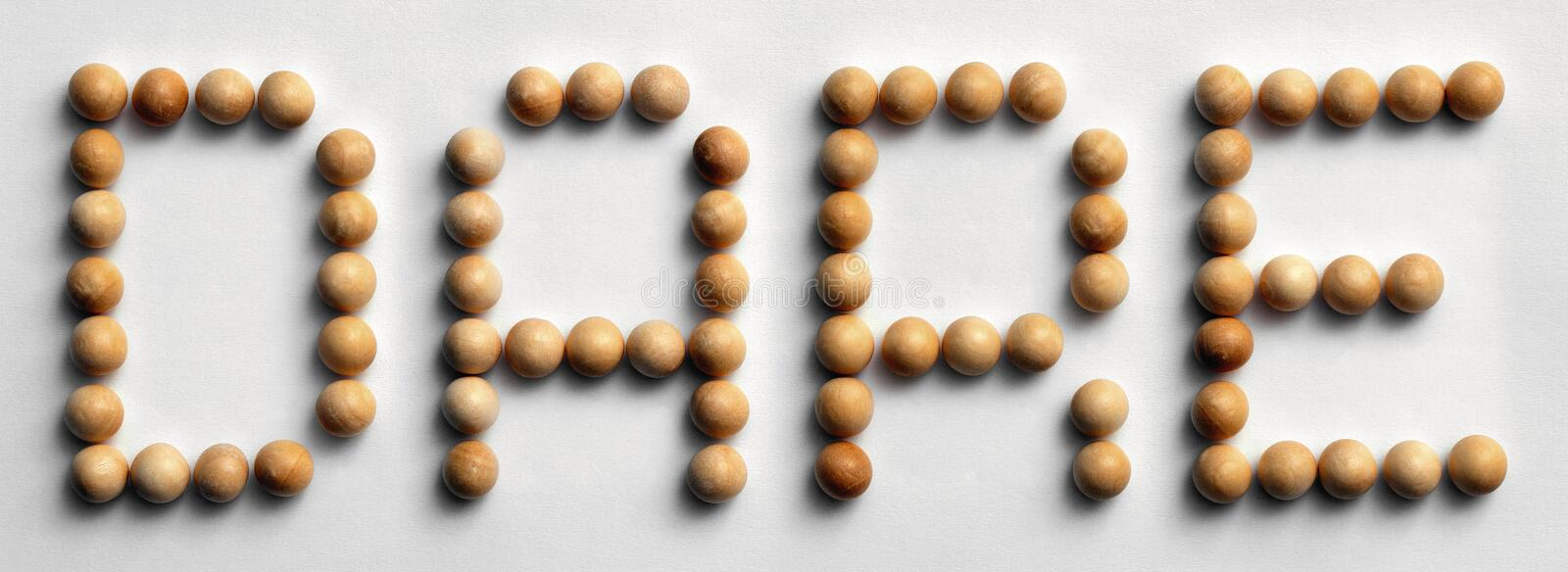 Wood Tack Word Art `Dare`. Photograph of the word `Dare` spelled out with wood push pins royalty free stock photos