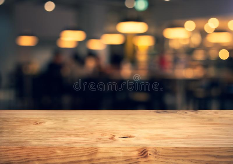 Wood texture table top counter bar with blur light gold bokeh in cafe,restaurant background.For montage product display or. Design key visual layout stock photo
