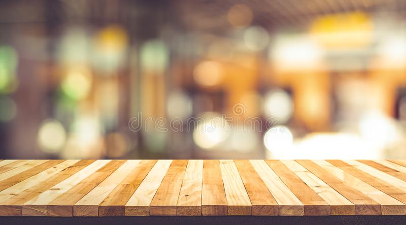Wood texture table top counter bar with blur light gold bokeh in cafe,restaurant background. For montage product display or design key visual layout royalty free stock image