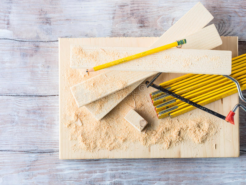 Wood and tools for measuring cutting level DIY craft. Wooden board with tools for manual measuring cutting - meter, level, pencil. Bricolage hand made DIY design royalty free stock image