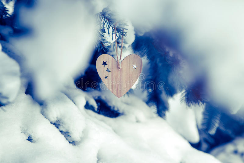 Of wood toys in the form of heart. Hanging in the branches of trees stock photo
