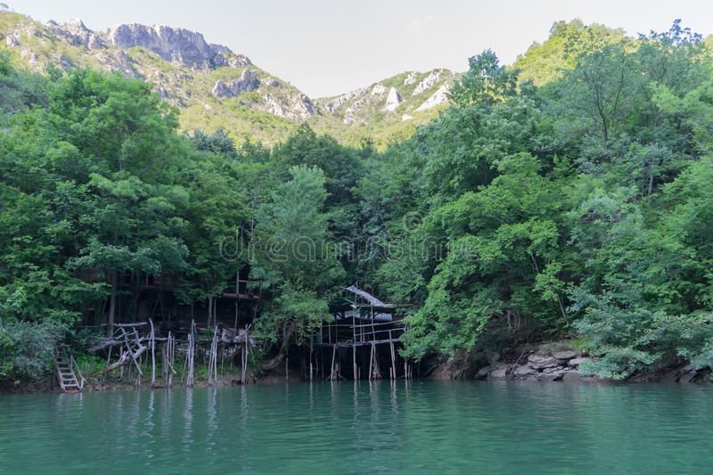 wood traditional house inside of the green forest and mountains and lake. Matka canyon in Macedonia with big rocks and peaks with royalty free stock photos