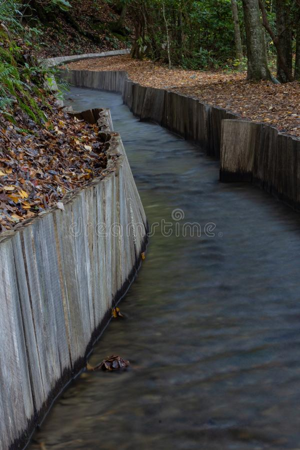Wood walled sluice winding through wooded area leading to an old mill. Vertical aspect stock images