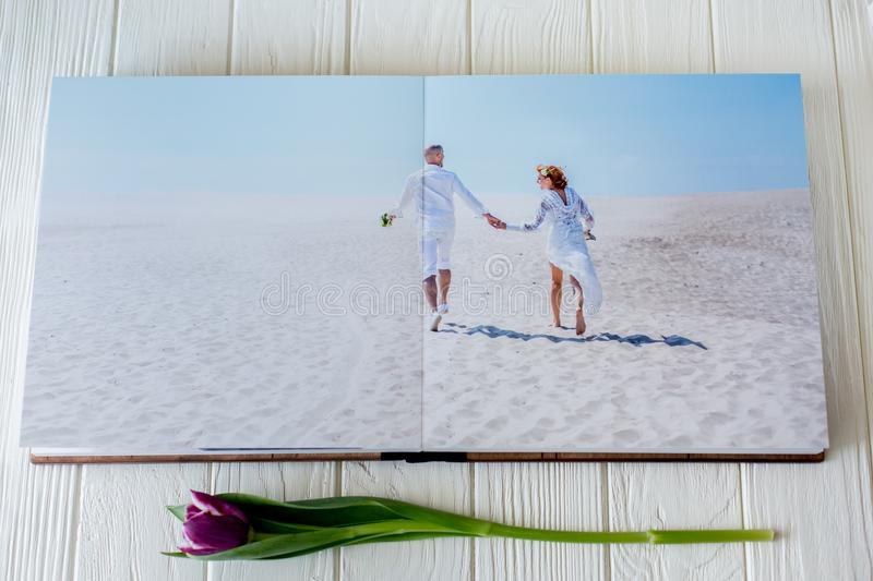 Wood wedding photo book. Happy young couple in love. Bride and groom walking of wedding day. royalty free stock images