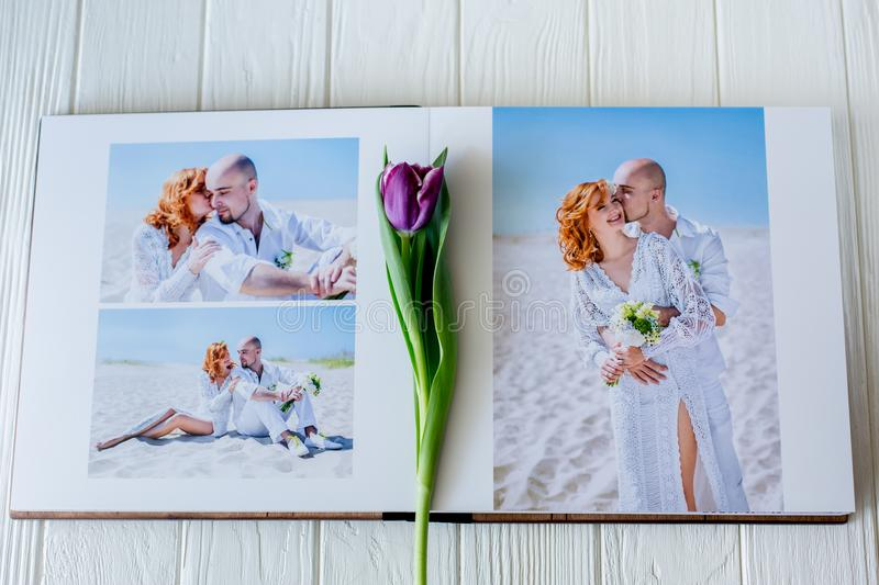Wood wedding photo book. Happy young couple in love. Bride and groom walking of wedding day. stock photos