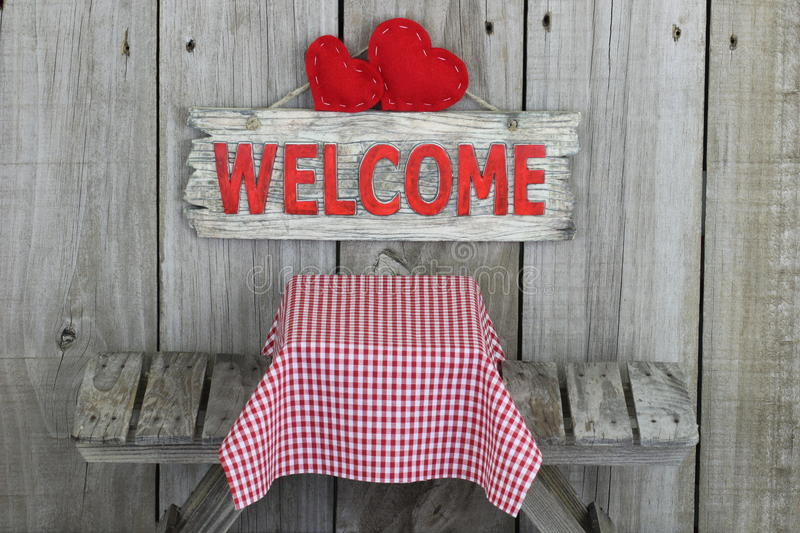 Wood welcome sign with hearts over picnic table royalty free stock photo