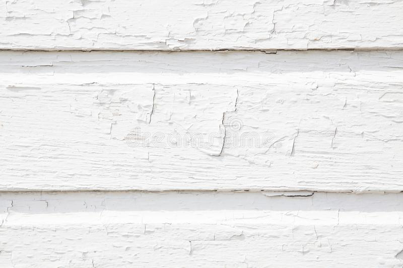Wood White Slat Wall with Cracking Paint. Closeup of a wooden slat wall with cracking and peeling white paint stock photos