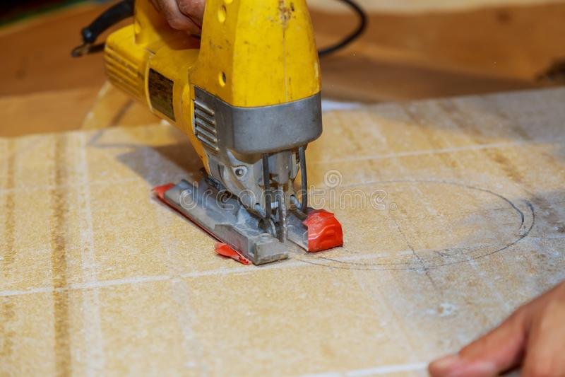 wood worker cutting wooden panel with jig saw outdoors, Close-up view of man stock photo