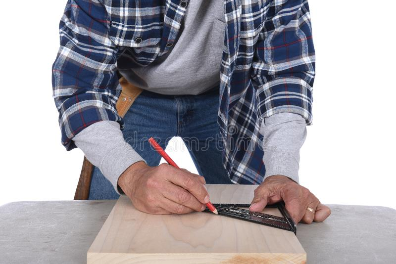 A wood worker marking a cut line on a board. Man is unrecognizable, isolated on white royalty free stock photo