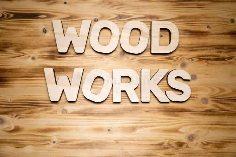 Wood works words made of wooden block letters on wooden board royalty free stock photo