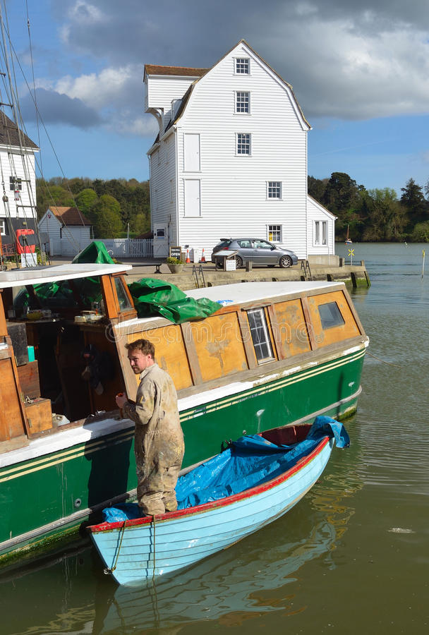 Man doing boat repairs at Woodbridge Quay. WOODBRIDGE, SUFFOLK, ENGLAND - APRIL 17, 2017: Man doing boat repairs at Woodbridge Quay with tide mill in the royalty free stock photo