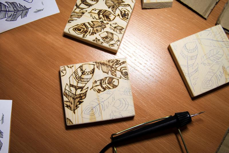 Woodburning. Burning on wood - a pattern with feathers on the li. D of the box stock image