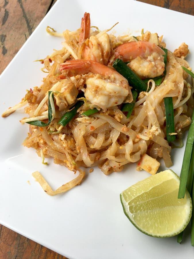 Woodden thailändsk ` för det thailändska Fried Noodles `-blocket med räka och grönsaker i den vita plattan på bakgrund Den av str royaltyfria bilder