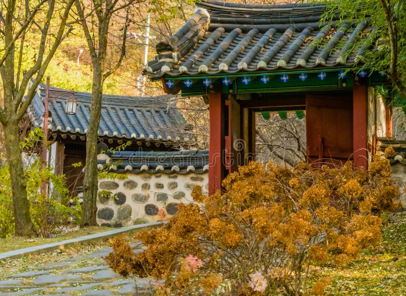 Wooded oriental gate with tiled roof. In urban public park with dead flowers and a stone walkway in Daejeon, South Korea royalty free stock image