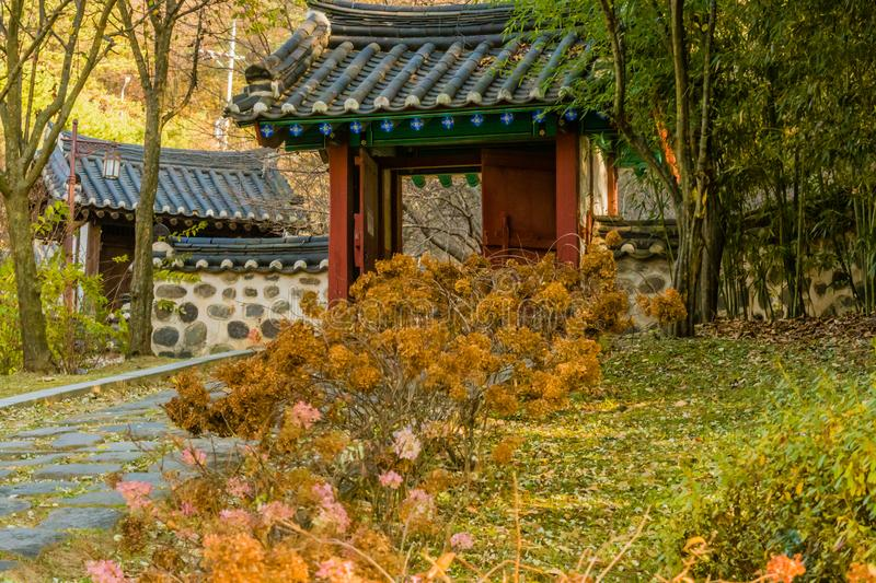 Wooded oriental gate with tiled roof. In urban public park with dead flowers and a stone walkway in Daejeon, South Korea stock photography