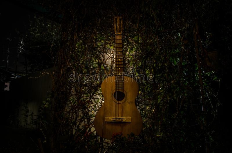 An wooden acoustic guitar is against a grunge textured wall. The room is dark with a spotlight for your copyspace. An wooden acoustic guitar at night. with stock photo