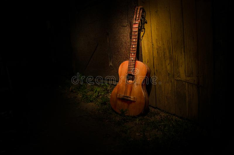 An wooden acoustic guitar is against a grunge textured wall. The room is dark with a spotlight for your copyspace. Old broken guitar royalty free stock image