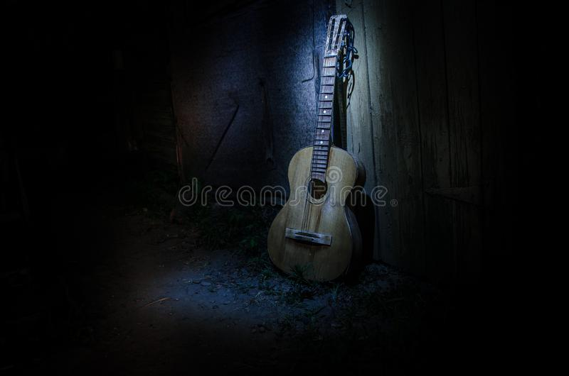 An wooden acoustic guitar is against a grunge textured wall. The room is dark with a spotlight for your copyspace. Old broken guitar royalty free stock photo