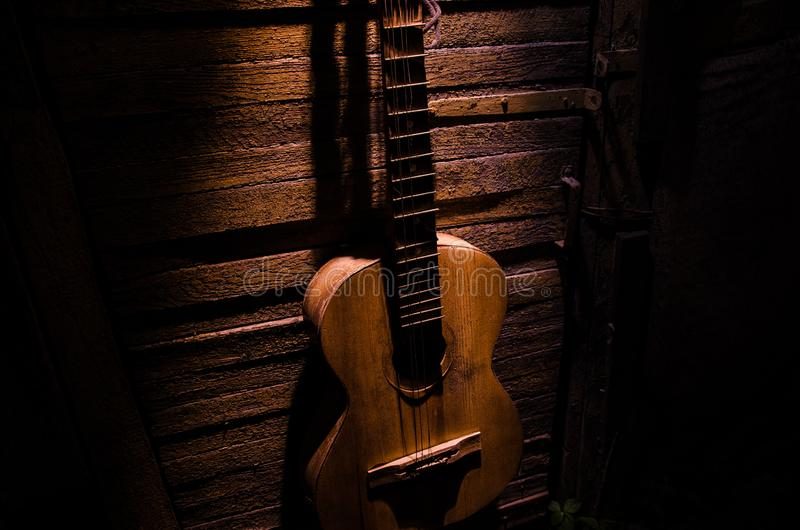 An wooden acoustic guitar is against a grunge textured wall. The room is dark with a spotlight for your copyspace. Old broken guitar royalty free stock images