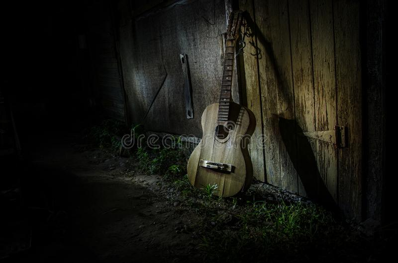 An wooden acoustic guitar is against a grunge textured wall. The room is dark with a spotlight for your copyspace. Old broken guitar stock image