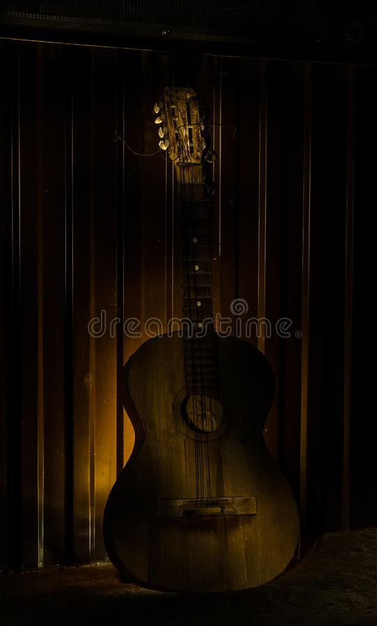 An wooden acoustic guitar is against a grunge textured wall. The room is dark with a spotlight for your copyspace. Old broken guitar royalty free stock photos