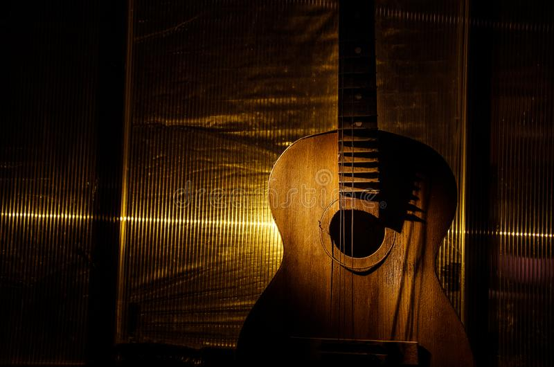 An wooden acoustic guitar is against a grunge textured wall. The room is dark with a spotlight for your copyspace. Old broken guitar royalty free stock photography