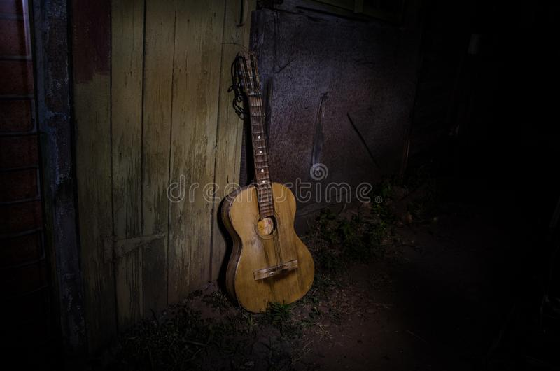 An wooden acoustic guitar is against a grunge textured wall. The room is dark with a spotlight for your copyspace. Old broken guitar stock photo
