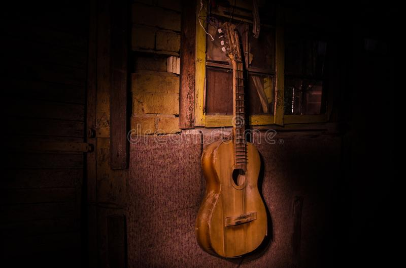 An wooden acoustic guitar is against a grunge textured wall. The room is dark with a spotlight for your copyspace. Old broken guitar stock images