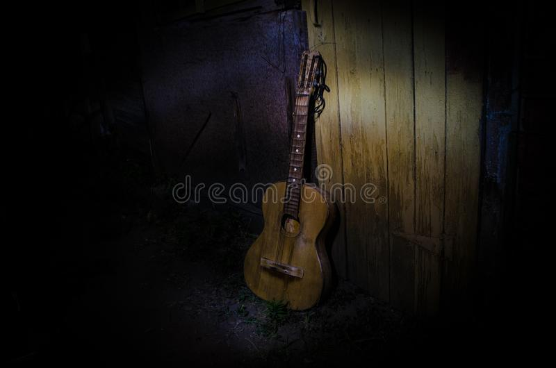An wooden acoustic guitar is against a grunge textured wall. The room is dark with a spotlight for your copyspace. Old broken guitar stock photos