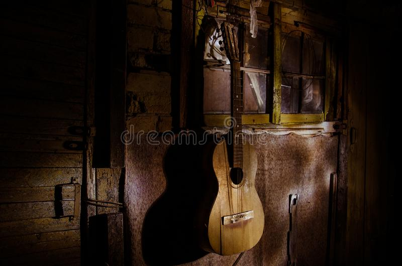 An wooden acoustic guitar is against a grunge textured wall. The room is dark with a spotlight for your copyspace. Old broken guitar stock photography