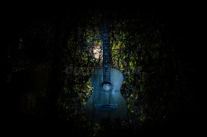 An wooden acoustic guitar is against a grunge textured wall. The room is dark with a spotlight for your copyspace. An wooden acoustic guitar at night. with royalty free stock image