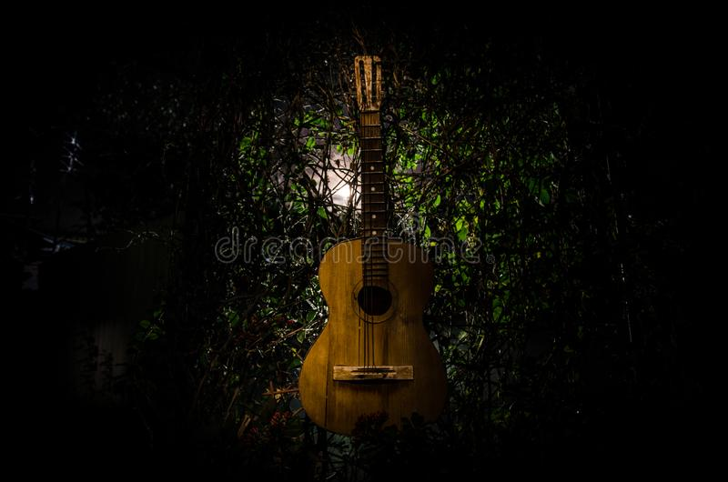 An wooden acoustic guitar is against a grunge textured wall. The room is dark with a spotlight for your copyspace. An wooden acoustic guitar at night. with stock photos