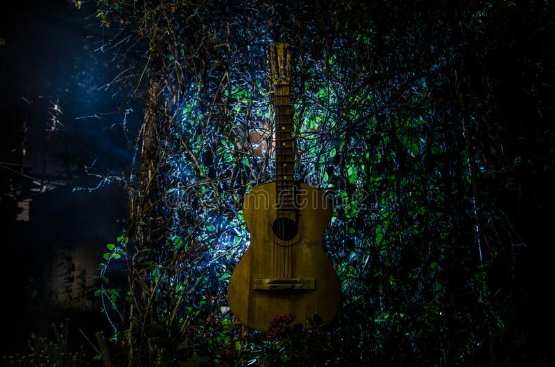 An wooden acoustic guitar is against a grunge textured wall. The room is dark with a spotlight for your copyspace. An wooden acoustic guitar at night. with royalty free stock images