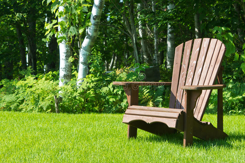 Wooden Adirondack summer lawn chair outside on the green grass. Adirondack summer lawn chair outside on the green grass stock image