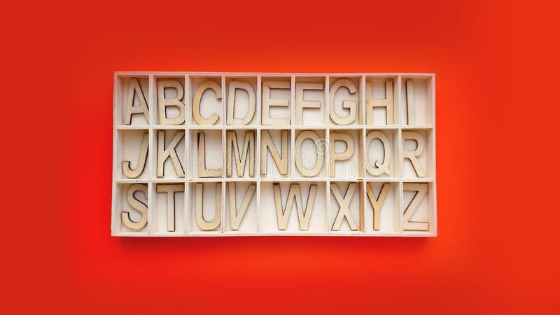 Wooden alphabet blocks with letters - box on a red background. Learning english stock photo