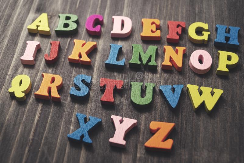 Wooden alphabet letters on wooden background. Retro royalty free stock photography