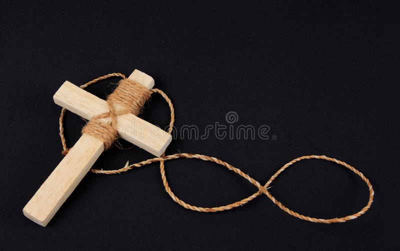 Wooden antique look crucifix necklace isolated. Onblack background stock image