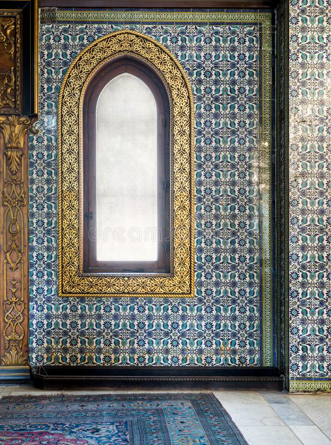 Wooden arched window framed by golden floral pattern ornaments over ceramic tiles wall with floral blue patterns. At the public mosque of The Manial Palace of stock image
