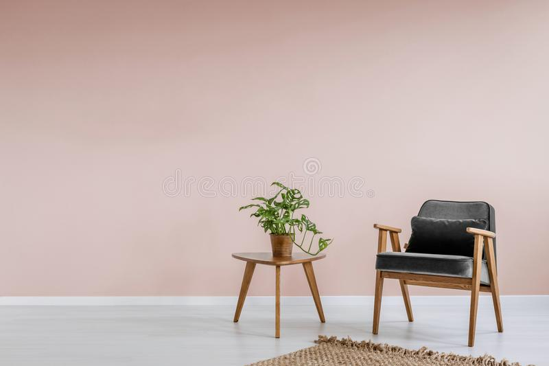 Wooden armchair with gray upholstery and a side table in a pastel pink living room interior with place for a bookcase. Real photo. Concept photo stock images